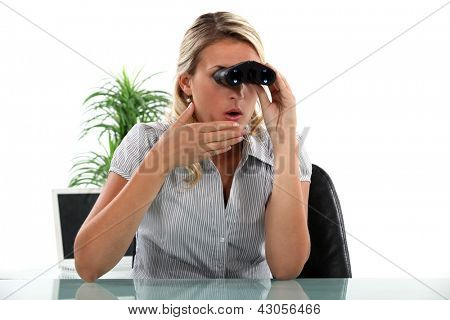 Office worker looking through a pair of binoculars