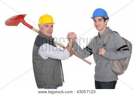 A construction worker and his apprentice shaking hands.