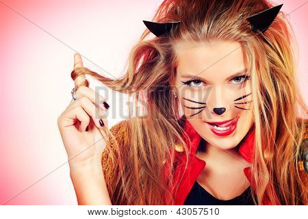 Portrait of a sexy girl in pussycat costume alluring over pink background.