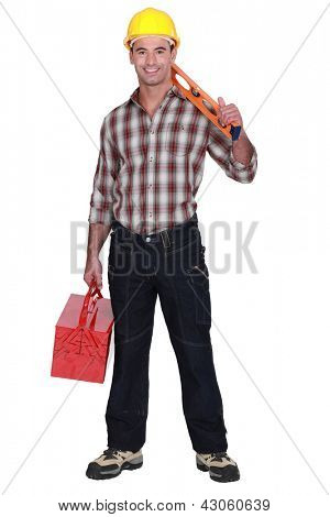 Construction worker holding a toolbox and spirit level