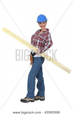 portrait of young female carpenter holding lumber