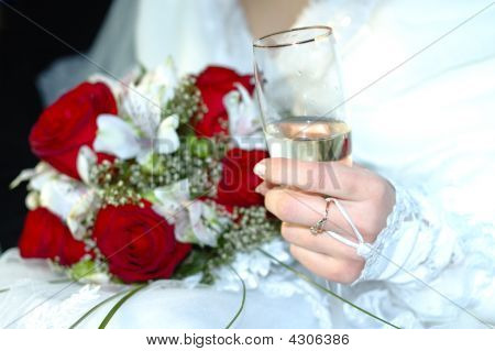 Bride With Wedding Bouquet And Glass Of Champagne.