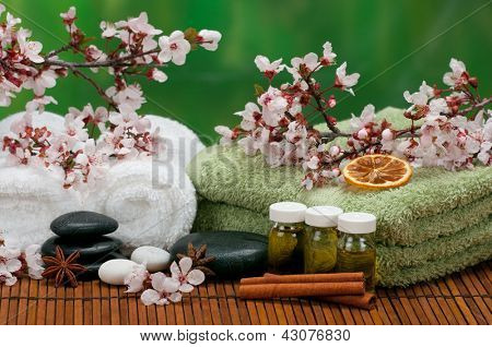Spa concept with massage oils, cotton towels, aromatic spices, and healing pebbles