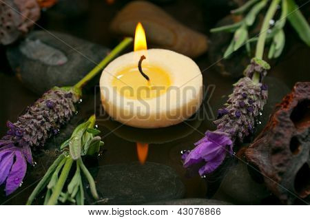 Spa concept with aromatic candles, lavender, healing pebbles and water