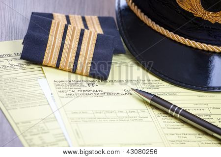 Close up of an airplane pilot equipment hat and epaluetes with medical forms and pen. Conceptual image of medical exam.