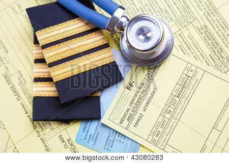 Close up of an airplane pilot equipment epaluetes with doctor's stethoscope, forms, medical and pilot certificate. Conceptual image of medical exam.