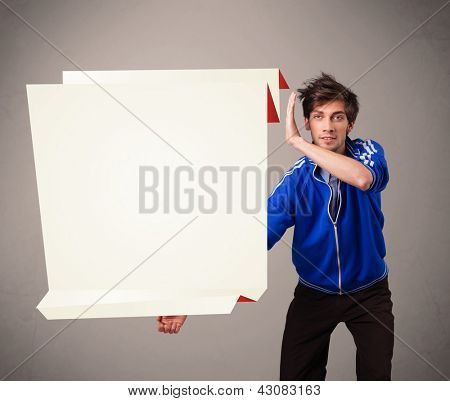 Handsome young man holding white origami paper copy space