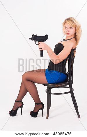 Pretty girl with gun on chair