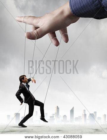 Businessman marionette on ropes controlled by puppeteer against city background