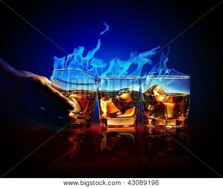 Image of three glasses of burning yellow absinthe