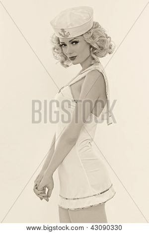 Duotone shot of young beautiful slim sexy girl with blond curly hair and stylish make-up dressed as sailor