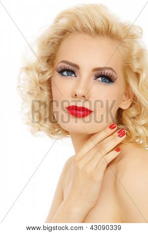 Young beautiful sexy blonde with stylish make-up and hairdo touching her face looking upwards