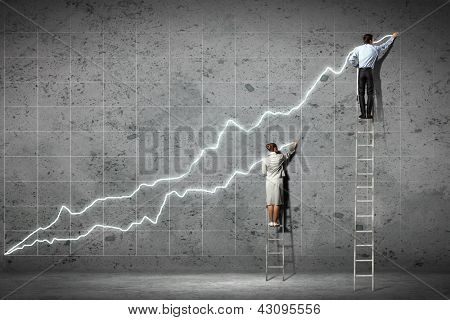 businesspeople standing on ladder drawing diagrams and graphs on wall