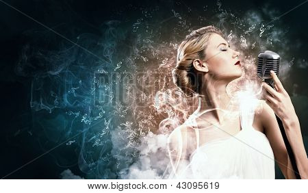 Image of female blonde singer holding microphone against smoke background with closed eyes