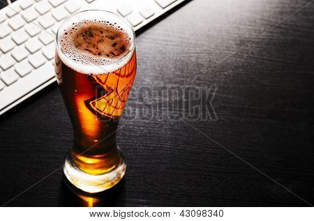 glass of fresh lager beer with keyboard on black table