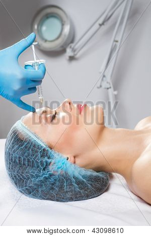 Young woman receiving a botox injection in her front