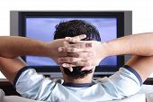 stock photo of watching movie  - A young adult watching TV in his home - JPG