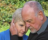 stock photo of grieving  - A senior couple holding each other close - JPG