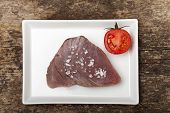 stock photo of yellowfin tuna  - raw tuna steak on a plate on wood - JPG