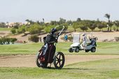 image of caddy  - Golf caddy trolley and bag on the fairway with buggy and bunker in the distance - JPG