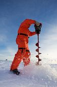 stock photo of auger  - Ice fisherman drilling a hole with a power auger - JPG