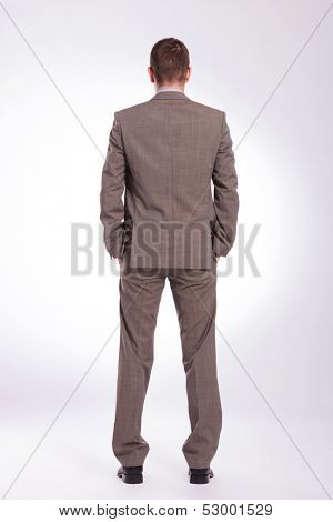 full length back view picture of a young business man standing with both hands in his pockets. on a gray background