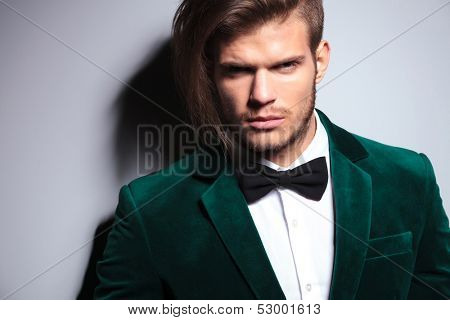 closeup picture of an attractive man with long hair wearing an elegant green suit and neck bow tie