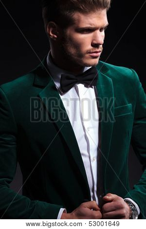side view of a fashion model in green velvet suit looking away from the camera while posing on black background