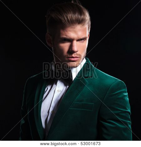 serious face of a young fashion model wearing a green velvet coat and bow tie on black background