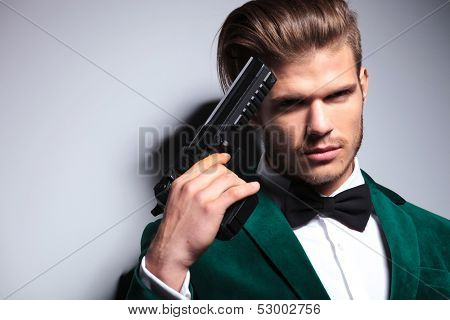 young assasin holding his gun against his head, closeup picture