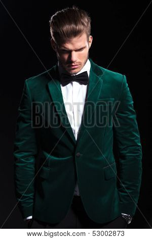 young man in a green velvet suit is looking down on black background