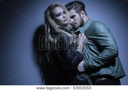 woman in leather jacket is pulling her lover closer and looks at the camera