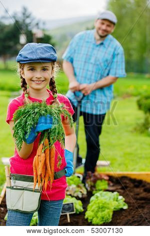 Gardening, planting, cultivation - lovely girl helping father in vegetable garden