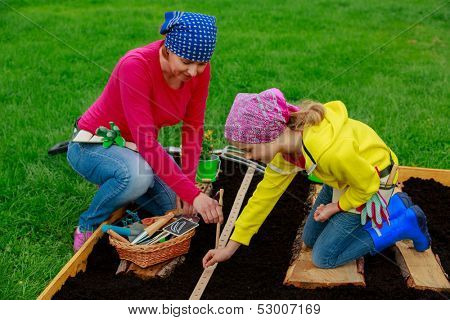 Gardening, sowing seeds to the soil-  girl helping mother in the garden