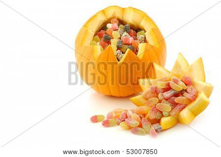 An orange Halloween pumpkin cut open and filled with candy on a white background