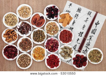 Traditional chinese herbal medicine with mandarin calligraphy  on rice paper. Translation describes the medicinal functions to maintain body and spirit health and balance energy.