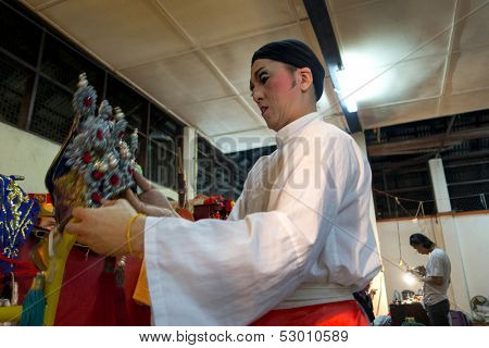 AMPANG - OCTOBER 9: A Chinese Opera actor prepares his head-dress before his act at the Kau Ong Yah Temple in Ampang, Malaysia on October 9, 2013; celebrating the nine emperor gods festival.