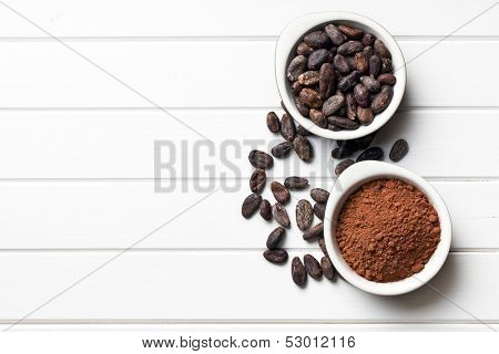 top view of cocoa beans and cocoa powder in bowls