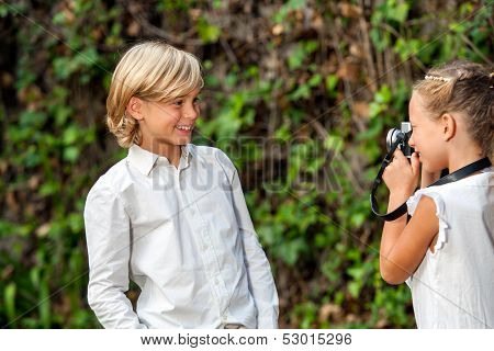 Girl Taking Pictute Of Boy Outdoors.