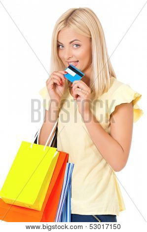 Shopaholic shopping woman with many shopping bags holding a credit card or gift card, isolated on white background
