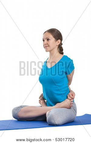 Yoga - young beautiful woman yoga instructor doing bound lotus pose (Baddha Padmasana) exercise isolated on white background