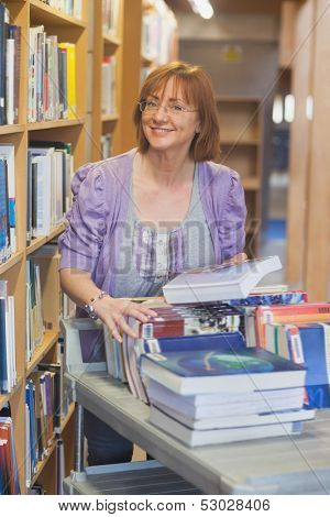 Female mature librarian returning books in library smiling at camera