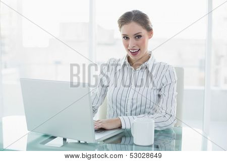 Gleeful lovely chic businesswoman sitting at her desk using her notebook smiling at camera