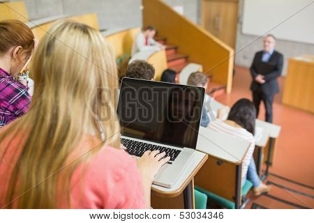 Rear view of a female using laptop with students and teacher at the college lecture hall
