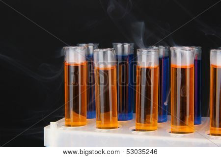 Laboratory test tubes on black background