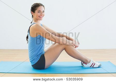 Full length portrait of a fit young woman sitting upright on exercise mat