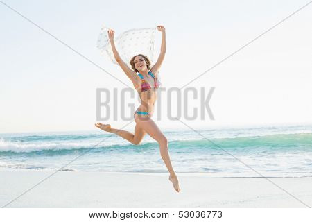 Euphoric slender woman jumping in the air holding shawl on the beach