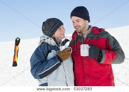 Happy loving couple having coffee with ski board on snow in background against clear blue sky