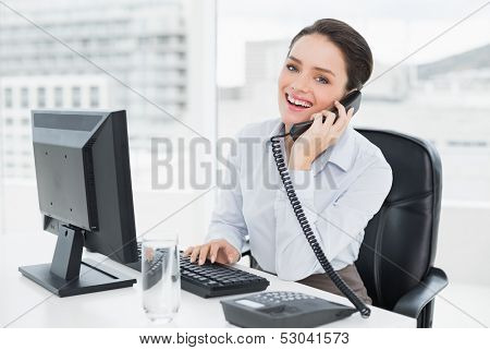 Portrait of a smiling elegant businesswoman using landline phone and computer in a bright office