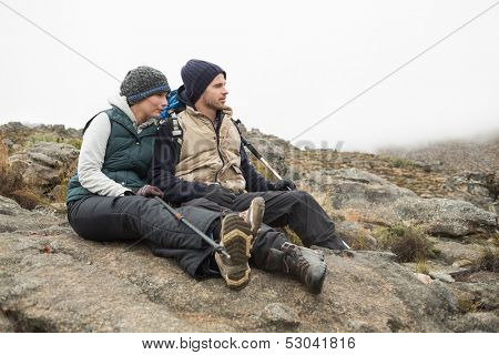 Full length of a young couple sitting on rock with backpack and trekking poles while on a hike